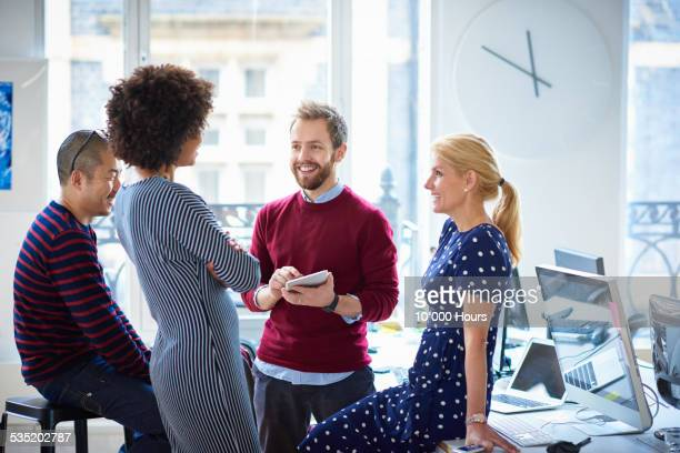 Smiling co-workers in informal meeting in office
