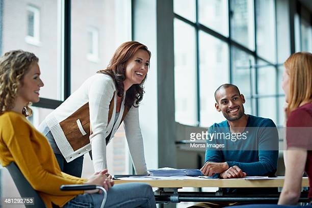smiling coworkers in meeting - employee engagement stock pictures, royalty-free photos & images