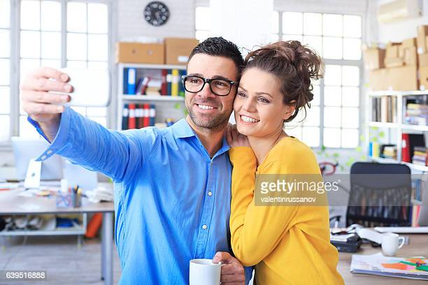 Smiling coworkers making selfie at workplace
