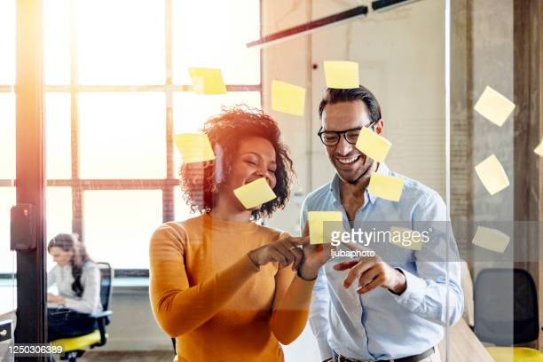 smiling coworkers writing tasks on sticky papers, post it notes - scrum stock pictures, royalty-free photos & images