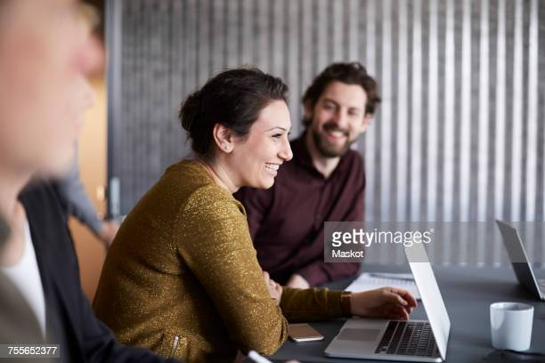 Smiling creative business team sitting with laptop at conference table in board room