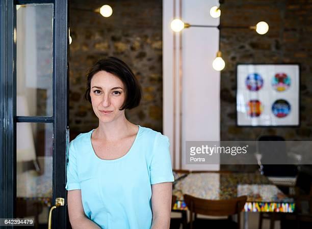 Smiling creative businesswoman standing at doorway