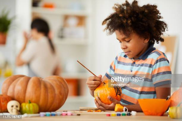 smiling creative child with afro hairstyle leaning on counter with gouaches and making design on pumpkin - carving craft product stock pictures, royalty-free photos & images