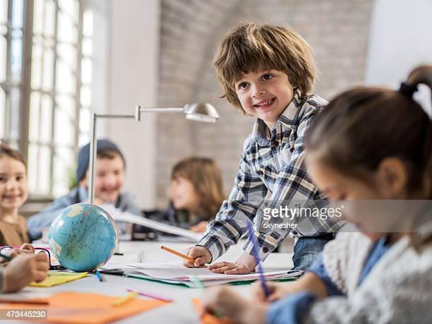 Lächelnd kreative kleine Junge sitzend am Tisch und Schreibtisch.