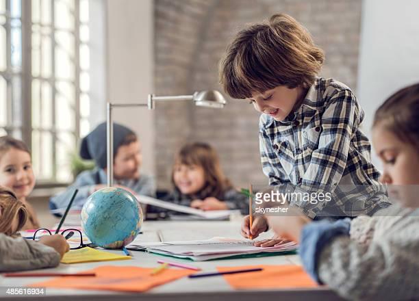 Smiling creative little boy sketching.