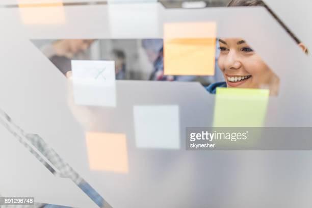 Lachende creatieve vrouw schrijven bedrijfsstrategie op zelfklevende notities in het kantoor.