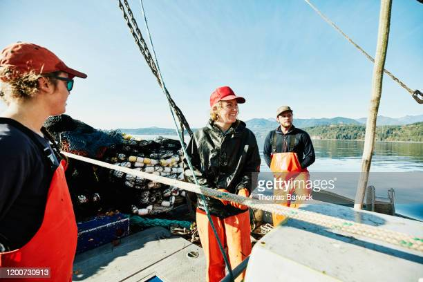 smiling crew members of fishing boat in discussion before setting net - crew stock pictures, royalty-free photos & images