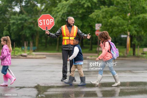 smiling crossing guard helps students safely cross street - crosswalk stock pictures, royalty-free photos & images