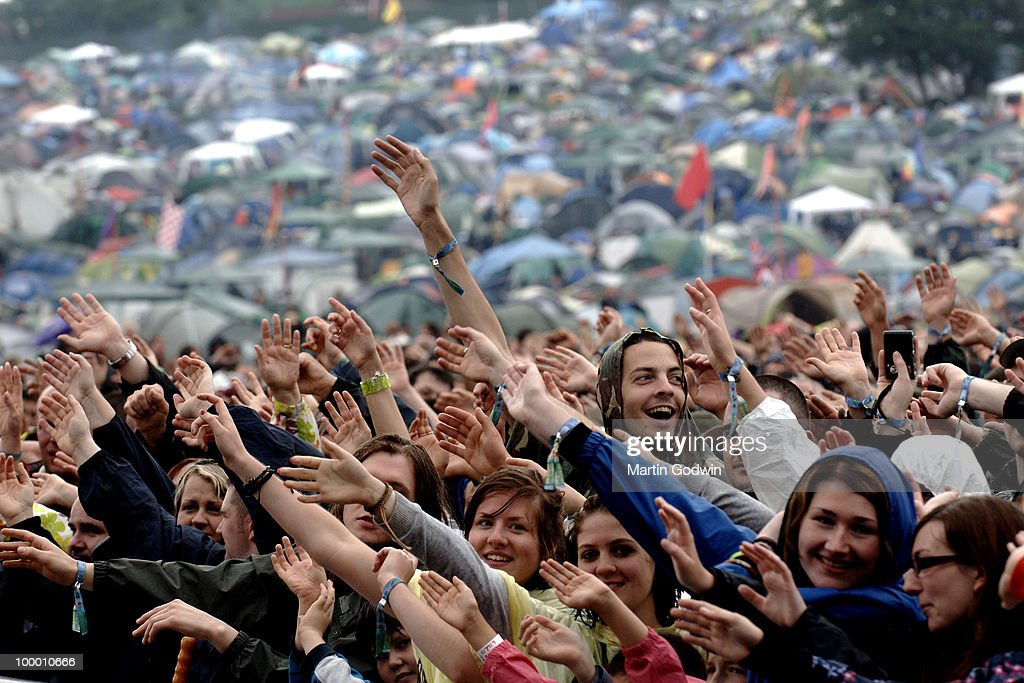 Smiling Crowds in front of the Pyramid Stage watching Bjorn Again, opening Glastonbury 2009, with tents in the distance, 26th June 2009.