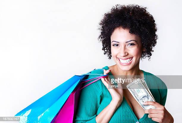 smiling curly-haired woman with shopping bags and cash