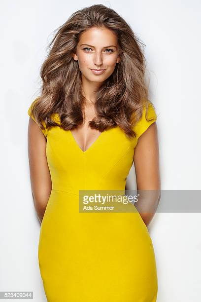 smiling curvy brunette in a yellow dress