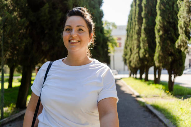 Smiling curvy young woman in a public park