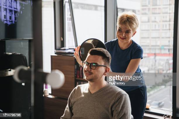 smiling customer at a barber shop with a new hairstyle - finishing stock pictures, royalty-free photos & images
