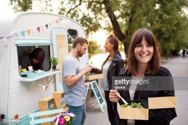 Smiling customer holding disposable salad box on street with friends and owner outside food truck in background