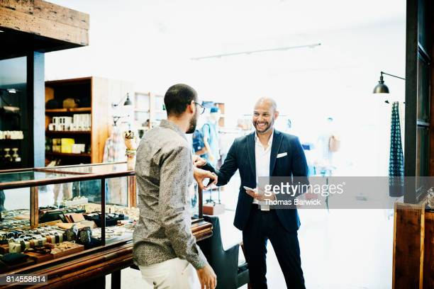 Smiling customer in discussion with shop owner in mens boutique
