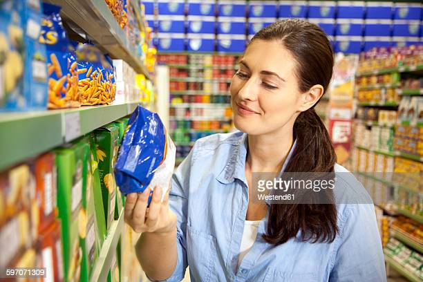 Smiling customer looking at a pack in a supermarket