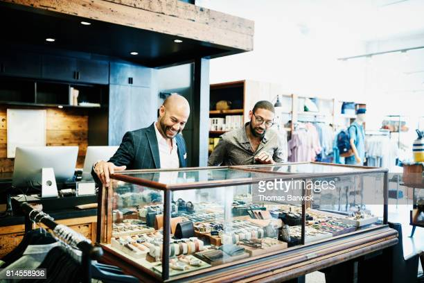 Smiling customer looking at mens accessories with shop owner in mens boutique