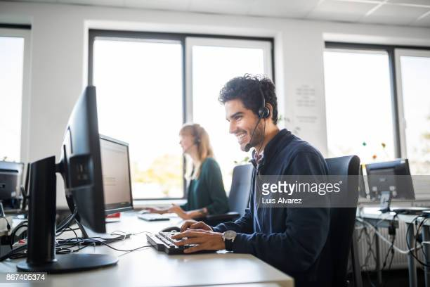 smiling customer service representative using computer at desk - call center stock pictures, royalty-free photos & images