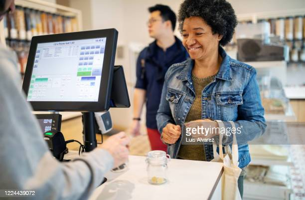 Smiling customer standing at checkout with owner at zero waste store