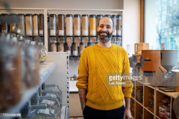smiling customer standing by rack at zero waste store - 40 44 jaar stock pictures, royalty-free photos & images