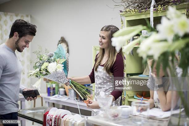 Smiling customer with florist in flower shop