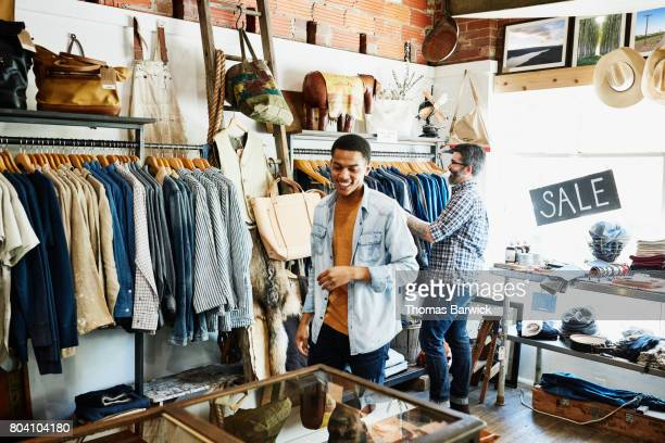 smiling customers shopping in mens boutique - boutique stock photos and pictures