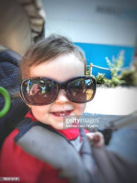 Smiling Cute Baby Girl Wearing Sunglasses While Sitting In Carriage