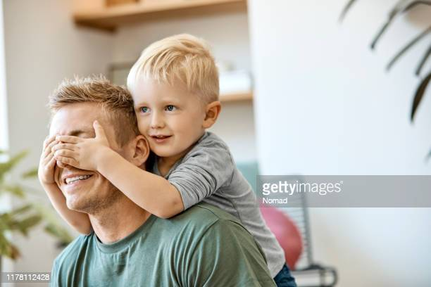 smiling cute blond boy covering eyes of father - nordic countries stock pictures, royalty-free photos & images