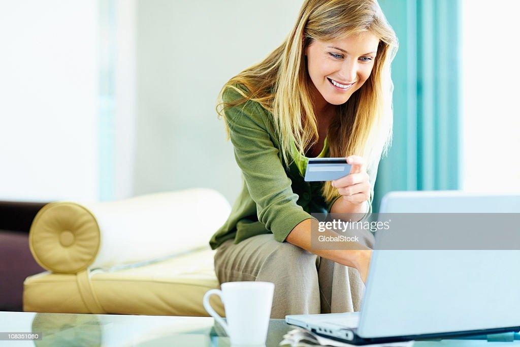 Linda mujer sonriente usando una tarjeta de crédito para compras en línea : Foto de stock