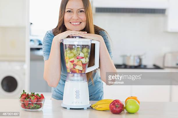 Smiling cute woman posing with a blender in kitchen