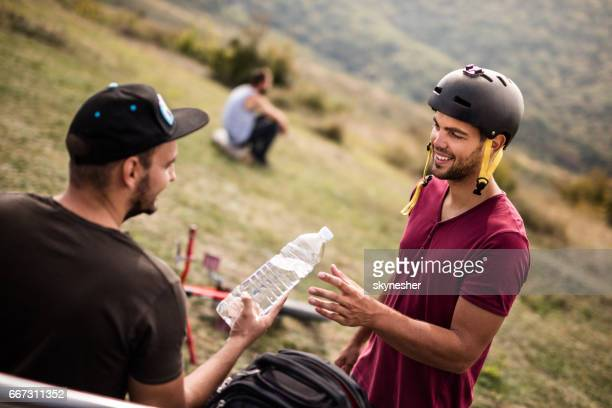 Smiling cyclist having a water break with friend in nature.