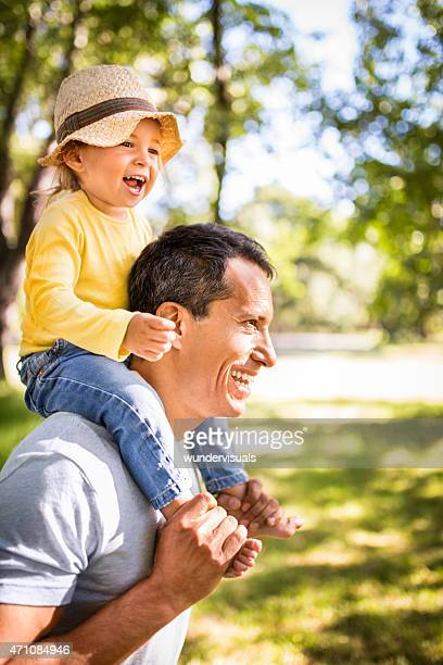 Smiling dad carrying his happy little girl on his shoulders
