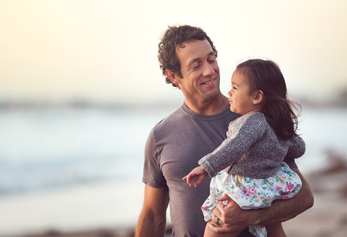 Smiling Dad Holds His Toddler Daughter Outdoors - gettyimageskorea