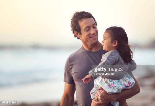 smiling dad holds his toddler daughter outdoors - één ouder stockfoto's en -beelden