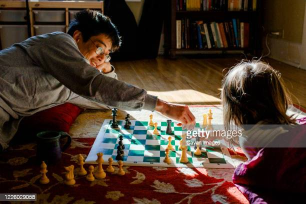 a smiling dad lays on floor with little girl playing chess in sunshine - chess stock pictures, royalty-free photos & images