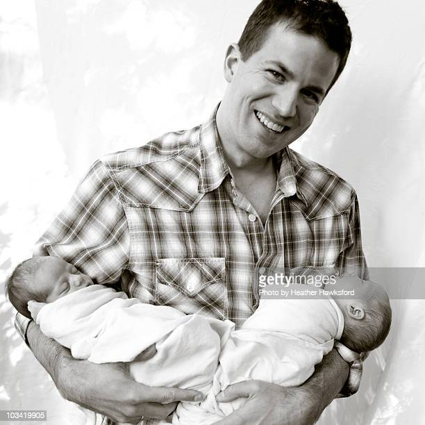 Smiling dad with newborn twins