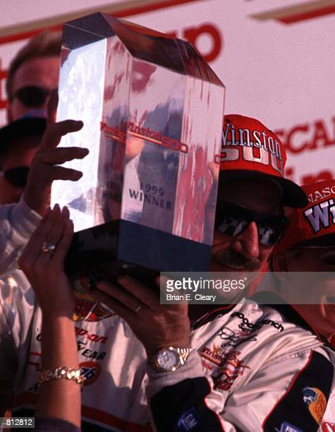 A smiling Dale Earnhardt holds his trophy after winning the Winston 500 at Talladega Alabama October 17 1999