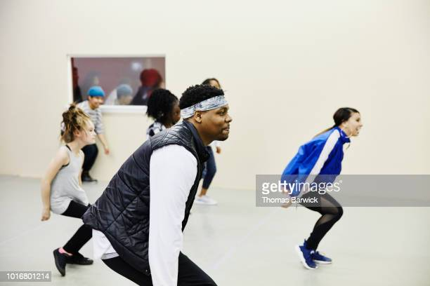 smiling dance instructor leading hip hop dance practice in dance studio - dance troupe stock photos and pictures