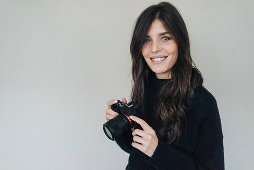 Smiling dark-haired young woman holding a camera - gettyimageskorea