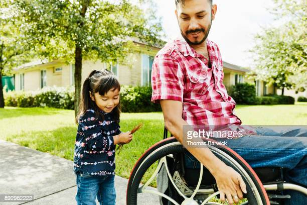 Smiling daughter and father in wheelchair walking through neighborhood on sunny afternoon