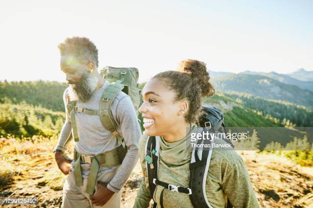 smiling daughter and father on backpacking trip on fall afternoon - holiday stock pictures, royalty-free photos & images