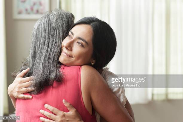 smiling daughter hugging mother - embracing stock pictures, royalty-free photos & images