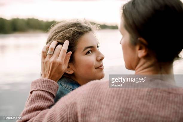 smiling daughter looking at caring mother by lake - daughter stock pictures, royalty-free photos & images