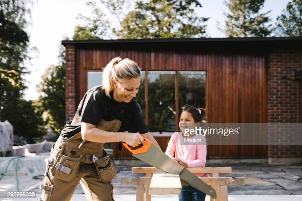 smiling daughter looking at mother cutting plank with hand saw against house - cutting stock pictures, royalty-free photos & images