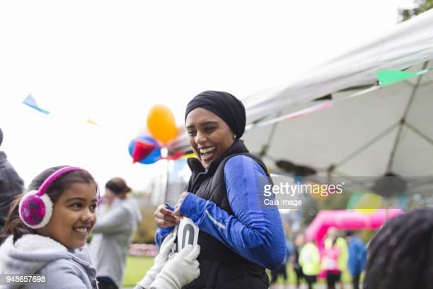 smiling daughter pinning marathon bib on mother at charity run - 40s pin up girls stockfoto's en -beelden