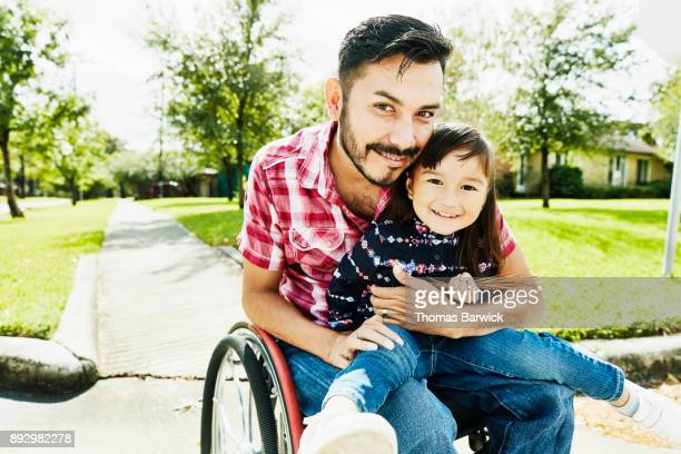 Smiling daughter sitting in fathers lap in wheelchair on sunny afternoon in neighborhood