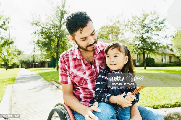 Smiling daughter sitting in fathers lap in wheelchair while out in neighborhood on sunny afternoon