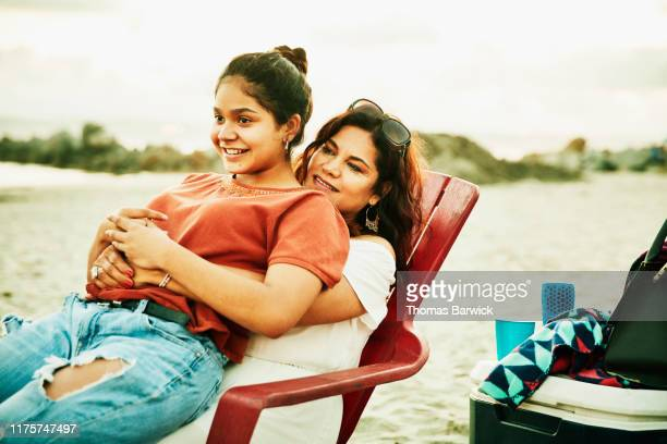 smiling daughter sitting on mothers lap during family beach party - trust stock pictures, royalty-free photos & images