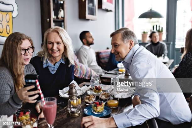 smiling daughter taking selfie with parents while sitting at table in restaurant - 18 19 años fotografías e imágenes de stock