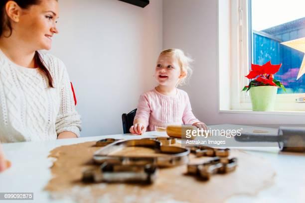 Smiling daughter talking to mother while preparing cookies